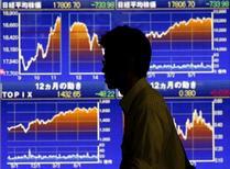 Мужчина у брокерской конторы в Токио. 25 августа 2015 года. Фондовый рынок Японии вырос в четверг, поскольку укрепление доллара к иене продолжило повышать аппетиты к риску, а Банк Японии сохранил текущий объем программы скупки активов. REUTERS/Issei Kato