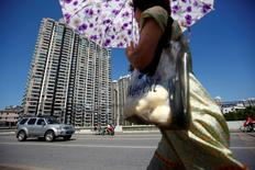 A woman walks past a residential site in Shanghai September 21, 2010.  REUTERS/Aly Song