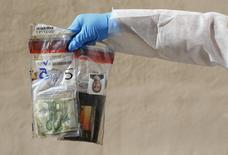 A member of the homicide squad holds plastic evidence bags containing unclaimed items, including photos, money and a travel pass, that belonged to a migrant who died during their journey to Europe, in the police department in Palermo, Italy November 4, 2015. REUTERS/Tony Gentile