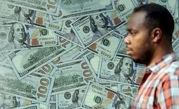Un hombre camina junto a una publicidad que muestra billetes de dólares estadounidenses, en El Cairo, 19 de noviembre de 2015. Los comentarios del presidente del Banco Central Europeo, Mario Draghi, hicieron caer el viernes medio punto porcentual al euro, hasta menos de 1,07 dólares, tras dos días de ganancias. REUTERS/Mohamed Abd El Ghany