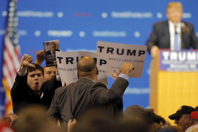 Supporters of U.S. Republican presidential candidate Donald Trump react as a protestor interrupts a campaign rally in Worcester, Massachusetts November 18, 2015.  REUTERS/Brian Snyder
