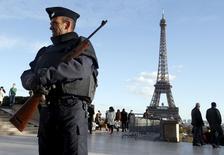 Полицейский охраняет Эйфелеву башню в Париже. 22 ноября 2015 года. Европейцы, которые решили не поддаваться панике после атак в Париже, могут утешиться - отклик на парижские события в экономике, который до сих пор был ограниченным, может и вовсе оказаться незначительным. REUTERS/Eric Gaillard