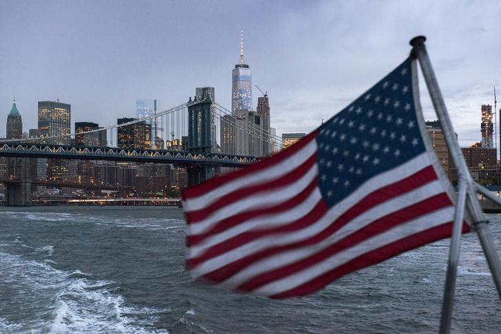 The Lower Manhattan skyline, One World Trade Center and Manhattan Bridge are seen in the background as a ferry with a U.S. flag cruises along the East River in New York September 21, 2015.    REUTERS/Darren Ornitz