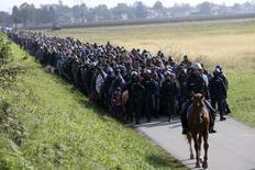 Полицейские сопровождают группу мигрантов в Словении. 20 октября 2015 года. Европейские страны находятся на пределе своих возможностей и больше не в состоянии принимать беженцев, заявил премьер-министр Франции Мануэль Вальс. REUTERS/Srdjan Zivulovic