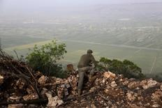 Сирийский боевик на холме в Латакии. 29 апреля 2015 года. Российские вооружённые силы начали массированную бомбардировку занятых боевиками районов сирийской провинции Латакия, недалеко от места крушения российского самолёта, который был сбит турецкой авиацией накануне, сообщили повстанцы и мониторинговая группа. REUTERS/Khalil Ashawi