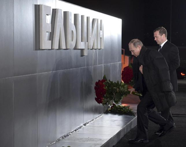 Russian President Vladimir Putin (L) and Prime Minister Dmitry Medvedev lay flowers at a monument of first Russian President Boris Yeltsin in Yekaterinburg, Russia November 25, 2015.  REUTERS/Alexander Astafyev/Sputnik/Pool