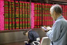 Un inversor mira su celular frente a un tablero electrónico que muestra la información de las acciones, en una correduría en Pekín, China, 16 de noviembre de 2015. Las acciones chinas cedieron unas ganancias iniciales y cerraron a la baja el jueves, luego de que un retroceso de los valores de baja capitalización en las operaciones de la tarde contrarrestó un fuerte rebote de las acciones ligadas a las materias primas. REUTERS/Li Sanxian