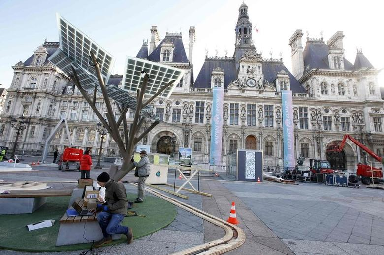 Employees work under solar panels during the installation of the exhibition ''Paris de L'Avenir'', a showcase for tangible climate solutions in the context of  the COP21 World Climate Summit, in front of Paris city hall, France, November 26, 2015. REUTERS/Eric Gaillard