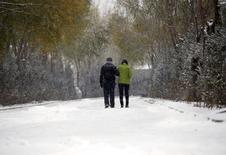 Fan Guohui (L) and his wife Zheng Qing walk in the snow after showing their son's resting place to reporters during their visit to the graveyard in Zhangjiakou, China, November 22, 2015.   REUTERS/Kim Kyung-Hoon
