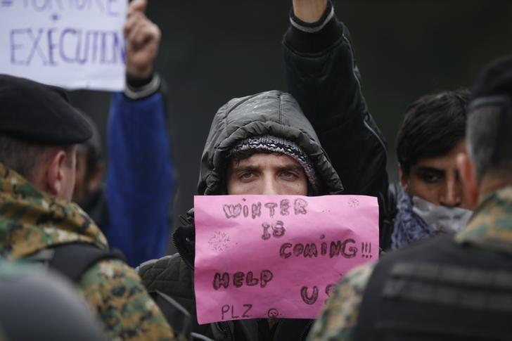 A migrant protests in front of police at the border with Greece, near Gevgelija, Macedonia November 25, 2015. Countries along the Balkan route taken by hundreds of thousands of migrants seeking refuge in western Europe last week began filtering the flow, granting passage only to those fleeing conflict in Syria, Iraq and Afghanistan.   REUTERS/Stoyan Nenov