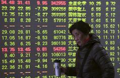 Un inversor camina junto a un tablero electrónico que muestra la información de las acciones en una correduría en Hangzhou, China, 27 de noviembre de 2015. Las bolsas chinas se hundieron más de un 5 por ciento el viernes en su mayor caída desde su desplome del verano boreal después de que Reuters reportó que el regulador bursátil local amplió su investigación sobre corredurías para incluir a la cuarta firma de valores más grande del país. REUTERS/Stringer