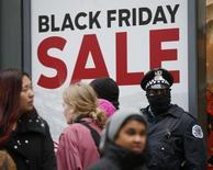 Policial para em frente a uma loja em Chicago, enquanto consumidores passam durante um protesto  motivado pela morte do adolescente negro Laquan McDonald, por um policial no ano passado. 27/11/2015. REUTERS/Jim Young