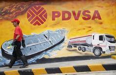 La estatal Petróleos de Venezuela (PDVSA) dijo el viernes que no ha sido notificada de la demanda interpuesta en su contra por la minera canadiense Crystallex, que exigió el pago de unos 2.800 millones de dólares en compensación por una expropiación. Imagen de archivo de un hombre caminando cerca de un mural con el logo de PDVSA en Caracas. 29 de agosto, 2014. REUTERS/Carlos García Rawlins