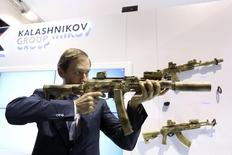 Russian Industry and Trade Minister Denis Manturov aims a weapon during the International Defence Exhibition (IDEX) in Abu Dhabi February 22, 2015. Russian firearms maker Kalashnikov Concern aims to concentrate on its markets in the Middle East and Africa and diversify its product range to offset the impact of Western sanctions, its chief executive said on Sunday. REUTERS/ Stringer (UNITED ARAB EMIRATES - Tags: POLITICS MILITARY BUSINESS)