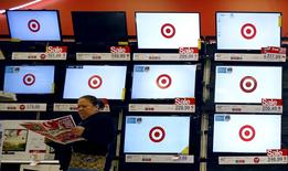 """Покупательница изучает рекламу распродажи во время """"Черной пятницы"""" в магазине Target в Чикаго.  Объём продаж в США в сезон предрождественского шопинга может вырасти на 3,7 процента в текущем году благодаря большому наплыву покупателей в выходные после Дня благодарения и """"Чёрной пятницы"""", а также благодаря успешным онлайн-продажам, сообщила Национальная федерация ритейлеров США (NRF), ссылаясь на данные ежегодного исследования. REUTERS/Jim Young"""