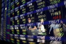 Transeúntes se reflejan en un tablero electrónico que muestra la información de las acciones, afuera de una correduría en Tokio, 25 de agosto de 2015. Una ola de ventas de las acciones chinas lastraba el lunes a los mercados de Asia, y el yuan rebotaba por una supuesta intervención de Pekín horas antes de que el FMI decida si incluirá a la moneda china en una canasta de monedas de reserva. REUTERS/Issei Kato