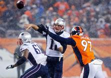 New England Patriots quarterback Tom Brady (12) throws the ball under pressure from Denver Broncos defensive end Malik Jackson (97) during the second half at Sports Authority Field at Mile High. The Broncos won 30-24. Mandatory Credit: Chris Humphreys-USA TODAY Sports