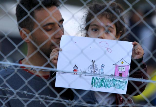 A young migrant girl holds up a drawing in a makeshift camp on the Macedonian-Greek border, near Gevgelija, Macedonia, November 30, 2015.  REUTERS/Ognen Teofilovski