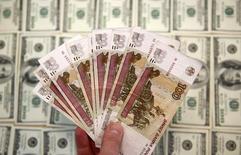 Рублевые и долларовые банкноты. Сараево, 9 марта 2015 года. Рубль подешевел в четверг, и если он обновил 2,5-месячное дно в паре с долларом из-за низкой рублевой цены на нефть, то против евро вышел к 2-месячным минимумам из-за ЕЦБ, не ставшего увеличивать ежемесячный объем скупки активов, и после комментариев главы ФРС, не добавившей ничего нового к своему выступлению накануне. REUTERS/Dado Ruvic