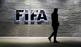 A journalist walks in front of FIFA's headquarters in Zurich, Switzerland December 2, 2015.    REUTERS/Arnd Wiegmann