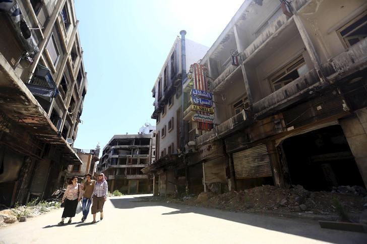 Women walk past damaged buildings along a street in the old city of Homs June 3, 2015.  REUTERS/Omar Sanadiki/Files