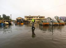 A man carries drinking water in a pitcher through a flooded street in Chennai, December 4, 2015. REUTERS/Anindito Mukherjee