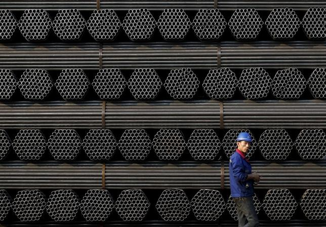A worker walks past a pile of steel pipe products at the yard of Youfa steel pipe plant in Tangshan in China's Hebei Province November 3, 2015. REUTERS/Kim Kyung-Hoon