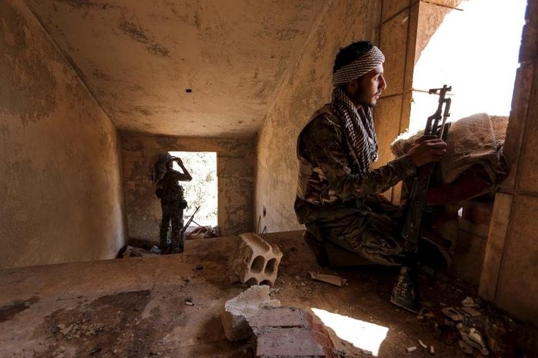 Kurdish People's Protection Units (YPG) fighters take up positions inside a damaged building in al-Vilat al-Homor neighborhood in Hasaka city, as they monitor the movements of Islamic State fighters who are stationed in Ghwayran neighborhood in Hasaka city, Syria July 22, 2015. REUTERS/Rodi Said