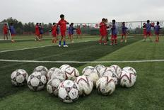 Students warm up before a training session at Evergrande soccer academy in Qingyuan, southern China December 4, 2015. REUTERS/Tyrone Siu