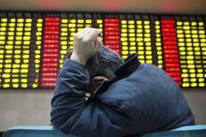 Un inversor frente a un tablero electrónico que muestra la información de las acciones, en una correduría en Nanjing, China, 8 de diciembre de 2015. Las acciones de Shanghái registraron su mayor pérdida en 10 días, luego de que unos decepcionantes datos comerciales de China y la caída del precio del petróleo agitaron a los inversores. REUTERS/China Daily