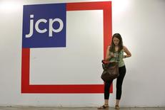 A woman checks her phone outside the entrance of a J.C. Penney store in New York August 14, 2013.  REUTERS/Brendan McDermid
