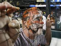 A Detroit Tigers baseball fan sporting face-paint leans into the infield fence as he waits out a rain delay that began prior to the start of Game 4 of the MLB ALCS baseball playoff series against the New York Yankees in Detroit, Michigan, October 17, 2012.  REUTERS/Jessica Rinaldi