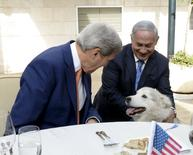 Israeli Prime Minister Benjamin Netanyahu (R) shows U.S. Secretary of State John Kerry his recently adopted dog Kaiya, during their meeting in Jerusalem November 24, 2015. Netanyahu's recently adopted dog Kaiya has sunk her teeth into her new position, biting two visitors at an event on December 9, 2015, including the husband of the deputy foreign minister. Picture taken November 24, 2015. REUTERS/Matty Stern/U.S. Embassy Tel Aviv/Handout    ATTENTION EDITORS - THIS IMAGE HAS BEEN SUPPLIED BY A THIRD PARTY. IT IS DISTRIBUTED, EXACTLY AS RECEIVED BY REUTERS, AS A SERVICE TO CLIENTS.  FOR EDITORIAL USE ONLY. NOT FOR SALE FOR MARKETING OR ADVERTISING CAMPAIGNS