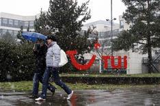 Люди проходят мимо логотипа TUI AG в Ганновере 25 марта 2009 года. Крупнейшая в мире туристическая компания TUI Group отчиталась о росте годовой прибыли на 15,4 процента.  REUTERS/Christian Charisius