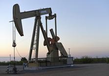 Una unidad de bombeo de petróleo operando cerca de Guthrie, Oklahoma, 15 de septiembre de 2015. Los mercados mundiales del petróleo tendrán un exceso de suministros al menos hasta fines del 2016 debido a una menor demanda y un auge en la producción de la OPEP, lo que presionará aún más a los precios, dijo el viernes la Agencia Internacional de Energía (AIE). REUTERS/Nick Oxford