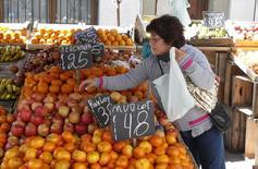 Una mujer comprando frutas en Montevideo, nov 6, 2015. El Fondo Monetario Internacional (FMI) bajó su previsión de crecimiento económico para Uruguay para este año y el próximo por un enfriamiento del consumo, la desaceleración de los vecinos Brasil y Argentina y la caída de los precios de las materias primas.    REUTERS/Andres Stapff