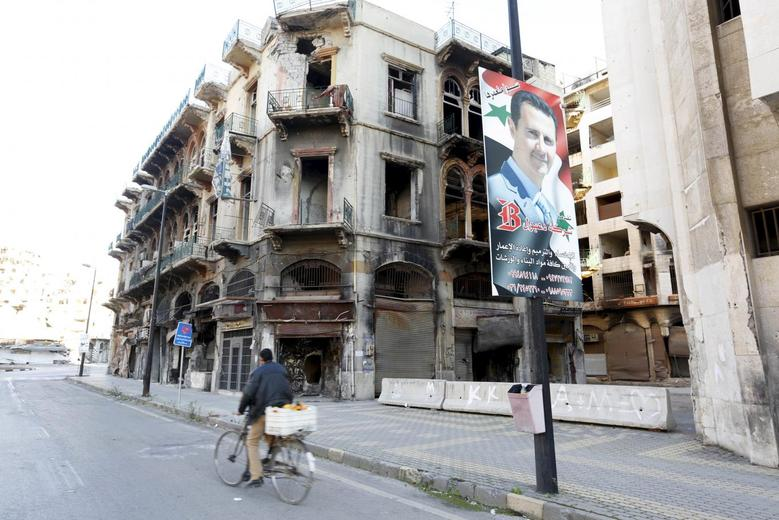 A man rides a bicycle past a poster depicting Syria's President Bashar al-Assad near the new clock square in the old city of Homs, Syria December 7, 2015.  REUTERS/Omar Sanadiki