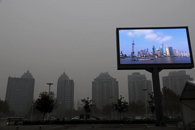 A electric screen showing Shanghai Pudong financial area in a clear day is seen amid heavy smog in Zhengzhou, Henan province, China, December 9, 2015. Picture taken December 9, 2015. REUTERS/Stringer
