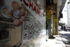 Мужчина выходит из пункта обмена валюты в Рио-де-Жанейро. 31 августа 2015 года. Курс доллара к корзине валют вырос на азиатской сессии в понедельник, основные валюты колеблются в узких пределах в преддверии заседания Федеральной резервной системы США на этой неделе. REUTERS/Ricardo Moraes