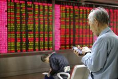 Inversores frente a un tablero electrónico que muestra la información de las acciones, en una correduría en Pekín, China, 16 de noviembre de 2015. Las acciones de Shanghái subieron más de un 2 por ciento el lunes en su mejor sesión en un mes, luego de que unos sólidos datos de actividad fabril en noviembre apoyaron la confianza sin echar por tierra las esperanzas de un nuevo estímulo de Pekín. REUTERS/Li Sanxian