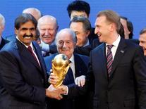 Qatar's Emir Sheikh Hamad bin Khalifa al Thani, Russia's Deputy Prime Minister Igor Shuvalov (R) and FIFA President Sepp Blatter hold a copy of the World Cup after the announcements that Russia and Qatar are going to be host nations for the FIFA World Cup 2018 and 2022 respectively, in Zurich December 2, 2010.   REUTERS/Christian Hartmann