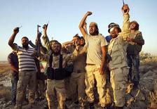 Бойцы оппозиционной сирийскому президенту Башару Асаду Свободной сирийской армии жестикулируют после взятия под контроль населенного пункта Тал аль-Заатар в провинции Дараа, Сирия, 13 августа 2015 года. Повстанцы опровергли получение поддержки от российских ВВС и заявили, что Россия, напротив, продолжает бомбить их. REUTERS/Alaa Al-Faqir