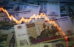 График колебаний курса доллара к рублю на фоне рублевых купюр в Варшаве 7 ноября 2014 года. Рубль в понедельник обновил минимумы 3,5 месяцев на фоне ускорившей падение к 11,5-летним минимумам нефти Brent, а также перед заседанием ФРС, итогом которого возможно повышение процентной ставки по доллару США. REUTERS/Kacper Pempel