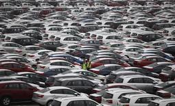 Workers walk between cars made by South Korea's biggest automakers Hyundai Motor Co and sister company Kia Motors at the company's shipping yard at a port in Pyeongtaek in this July 21, 2014 file photo.  REUTERS/Kim Hong-Ji
