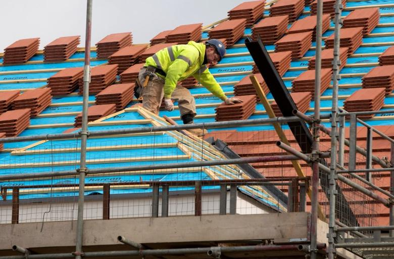 A builder works on the roof of a new residential property development in north London, March 21, 2013. REUTERS/Neil Hall