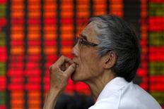 Un inversor mira un tablero electrónico que muestra la información de las acciones, en una correduría en Shanghái, 10 de julio de 2015. Las acciones chinas cerraron a la baja el martes, luego de que una corrección de los papeles ligados a la banca y a las materias primas contrarrestó un repunte de los valores del sector inmobiliario por la esperanza de más medidas de apoyo al mercado de bienes raíces. REUTERS/Aly Song