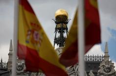 La deuda pública española cayó en el mes de octubre en unos 5.500 millones de euros respecto a septiembre, hasta 1,057 billones de euros, dijo el jueves el Banco de España.  En la imagen, la cúpula del Banco de España entre banderas españolas en el centro de Madrid el 19 de junio de 2013.  REUTERS/Sergio Pérez