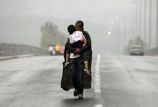 """Сирийский беженец с дочерью возле греческо-македонской границы. 10 сентября 2015 года. Число вынужденных переселенцев во всем мире, скорее всего, """"значительно превысило"""" рекордные 60 миллионов в этом году, в основном, в связи с войной в Сирии и другими затяжными конфликтами, сообщила ООН в пятницу. REUTERS/Yannis Behrakis"""