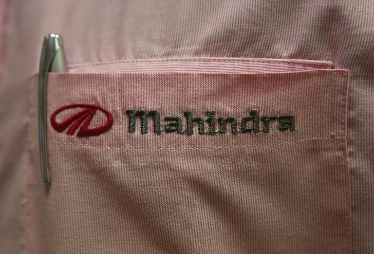 The logo of Mahindra & Mahindra Ltd is pictured on the pocket of a salesman's shirt as he poses inside the company's showroom in Mumbai August 13, 2013. REUTERS/Danish Siddiqui/Files