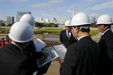 Japan Sport Council officials look at a map as they survey the site where the new national stadium, the centrepiece of the Tokyo 2020 Olympics, is to be built in Tokyo, November 16, 2015. REUTERS/Thomas Peter